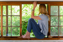 Woman Sitting In Window Looking Out To Greenery