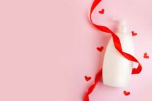 Cosmetics, Moisturizer, Shampoo Bottle With Red Hearts And Ribbon On Pink Background With Copy Space. Valentine's Day, Skin Care With Love