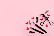 Black False Eyelashes And Tweezers On Pink Background With Red Hearts And Ribbon , Copy Space