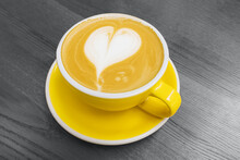 Yellow Cup Of Coffee With Heart Shaped Latte Art