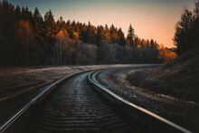 Railway Tracks In The Middle Of The Forest In Autumn At Sunset