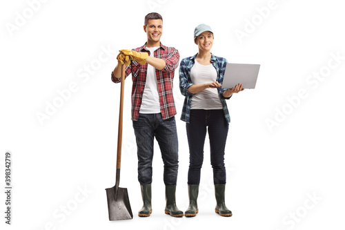 Obraz Full length portrait of modern farmers, male and female with a laptop computer - fototapety do salonu