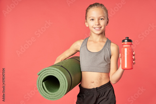 Canvas Print Cute sporty girl holding yoga mat and bottle of water