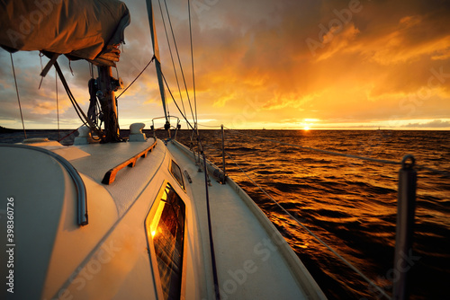 Fototapeta White yacht sailing in an open sea at sunset