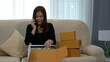 happy woman talking on a mobile phone and unboxing cardboard parcel box