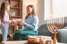 Happy Little Girl With Mother Celebrating Hannukah At Home
