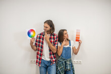 Young Couple Discussing The Color For Walls And Looking Uncertain
