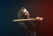 Portrait Of Young Blonde Beautiful Woman In A Leather Jacket With Wooden Baseball Bat Looks Into The Camera