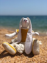 Hand-made Toy Bunny In A Knitted Dress Sitting On The Sand On The Beach. She Has Long White Ears And Beady Black Eyes.