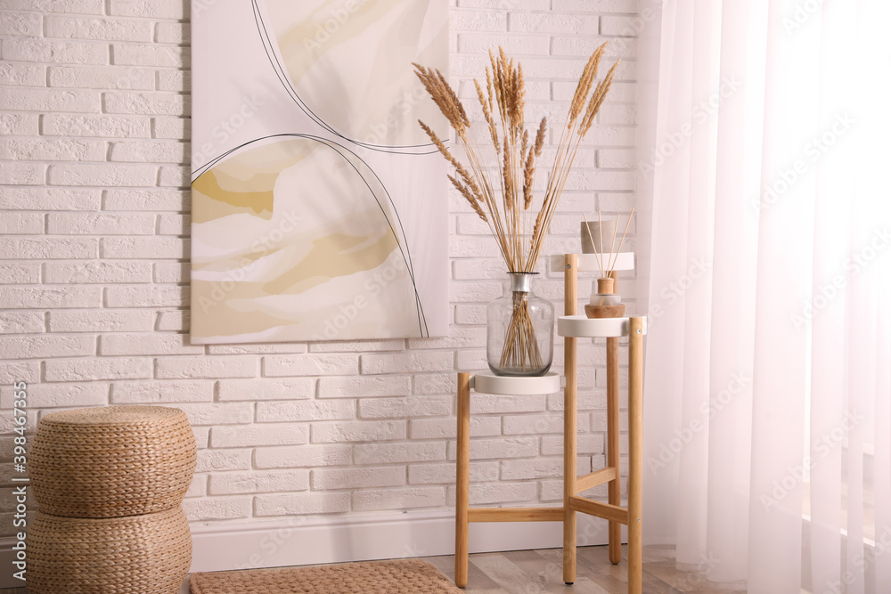Fototapeta Fluffy reed plumes and painting in stylish room interior