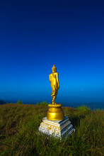 Golden Buddha Statue On Mountain With Blue Sky