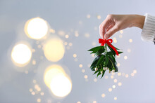 Woman Holding Mistletoe Bunch With Red Bow Against Blurred Festive Lights, Closeup And Space For Text. Traditional Christmas Decor