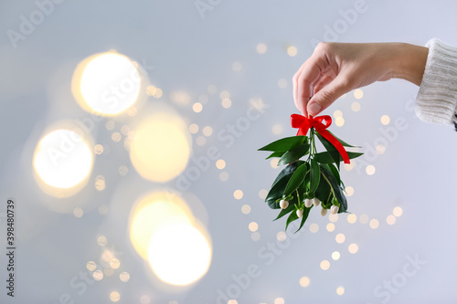 Obraz na płótnie Woman holding mistletoe bunch with red bow against blurred festive lights, closeup and space for text