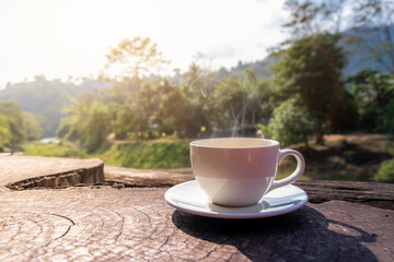 A white cup of hot espresso coffee mugs placed on a wooden floor with morning fog and moutains with sunlight background,coffee morning