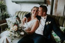 Industrial Wedding: Bride And Groom Sitting On A Vintage Sofa.