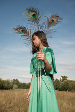 Girl In Vintage Green Dress Holding Three Peacock Feathers In A Field In Nature