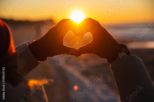 Obraz Woman hands in red winter gloves Heart symbol shaped Lifestyle, Winter Solstice and Feelings concept with sunset light nature on background - fototapety do salonu