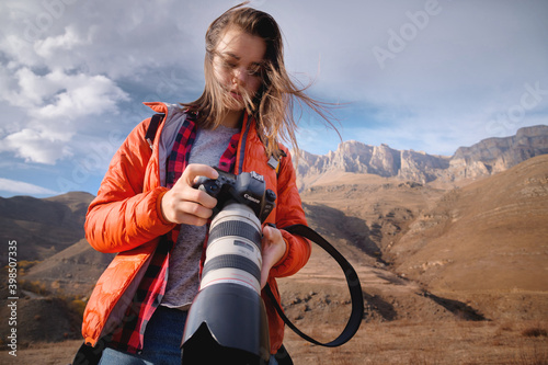Young attractive caucasian woman with a professional photo camera in her hands against the backdrop of epic high rocks high in the caucasus mountains. Photo tours and landscape photography