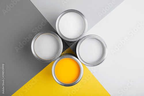 Demonstrating colors of year 2021 - Gray and Yellow. Four open cans of paint on bright symmetry background.Renovation concept. - fototapety na wymiar