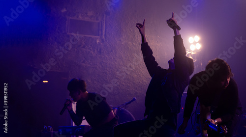 Fotografía Silhouette of Rock band with vocalist show hands raised up performing on stage, Rock concert show set up