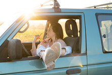 Young Woman Looking Away While Sitting With Feet Up On Car Window During Road Trip
