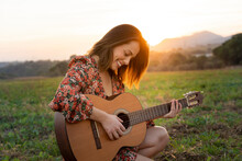 Smiling Young Woman Playing Guitar On Meadow During Sunset