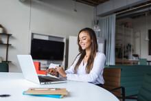 Smiling Businesswoman Using Latptop At Desk In Office