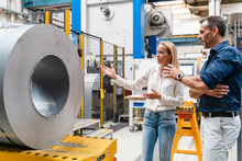 Female Entrepreneur And Male Colleague Examining Steel Roll While Standing In Factory