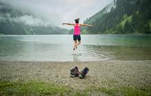 Excited Woman Jumping At Lakeshore During Rainy Season