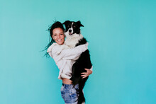 Happy Woman Carrying Border Collie Dog Against Turquoise Background