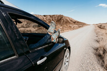 Spain, Navarre, Young Woman Sticking Legs Out Of Car Window Over Over Dirt Road In Bardenas Reales