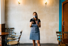 Female Cafe Owner Wearing Protective Face Mask While Using Digital Tablet Against Wall