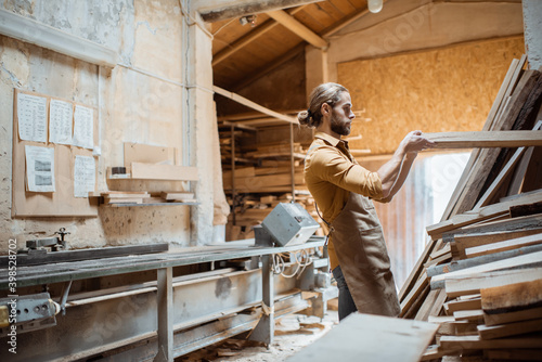 Obraz Carpenter or warehouse worker choosing raw wood material for the work at the carpentry storage - fototapety do salonu