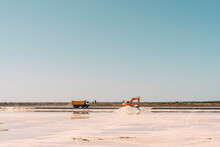 Spain, Province Of Huelva, Huelva, Clear Sky Over Truck And Earth Mover Working In Salt Flat