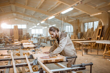 Handsome Carpenter In Uniform Gluing Wooden Bars With Hand Pressures At The Carpentry Manufacturing