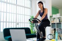 Young Woman Listening Music Through Bluetooth While Sitting On Exercise Bike At Home
