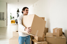Smiling Young Man Carrying Cardboard Box While Moving In New Apartment