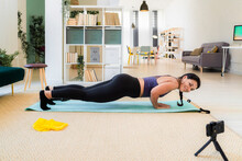 Young Fitness Woman Smiling While Video Recording On Camera Doing Push Ups At Home