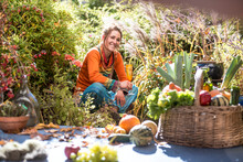 Smiling Woman Harvesting Fruit And Vegetable While Sitting In Garden