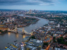 UK, England, London, Helicopter View Of River Thames, Tower Bridge And Surrounding Buildings At Dusk