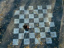 Mid Adult Woman Walking On Chessboard Painted On Asphalt