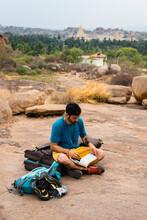Young Man Reading Book While Sitting On Land, Karnataka, Hampi, India