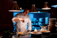 Male Chef Sprinkling Seasoning Seafood In Kitchen At Restaurant