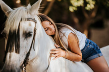 Beautiful Young Woman Leaning On Top Of White Horse