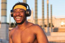 Shirtless Man Wearing Headphones Laughing While Standing At Park