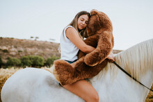 Portrait Of Beautiful Young Woman Embracing Large Teddy Bear While Sitting On Horseback With Closed Eyes