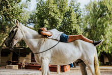 Beautiful Young Woman Lying On Top Of White Horse