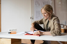 Smiling Businesswoman Using Digital Tablet While Sitting At Home