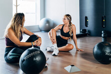 Female Friends Sitting In Gym With Medicine Ball