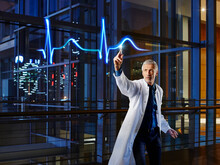 Male Cardiologist Light Painting Pulse Trace In Laboratory At Hospital